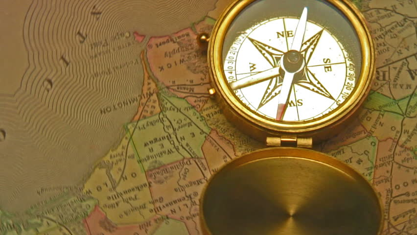 Old brass compass over antique map spinning around