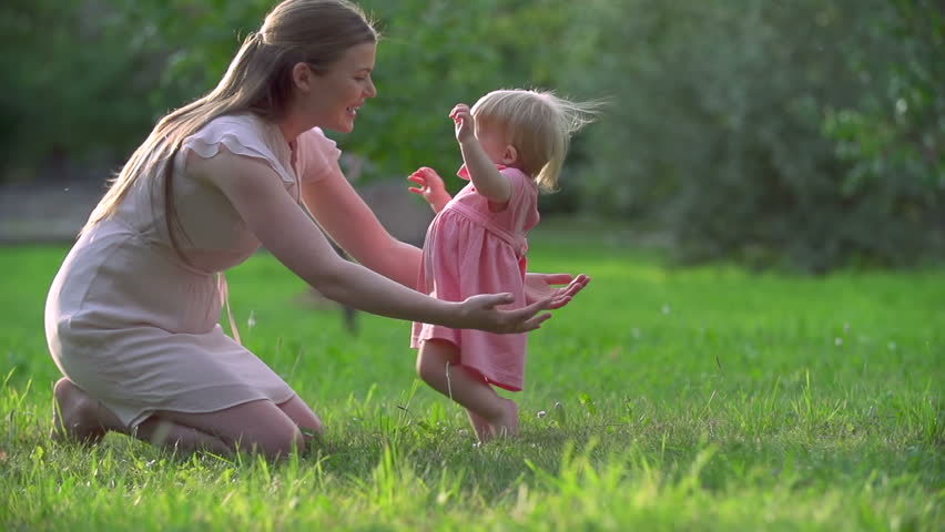 Adorable toddler hardly keeping balance in her first steps to mother #7250107