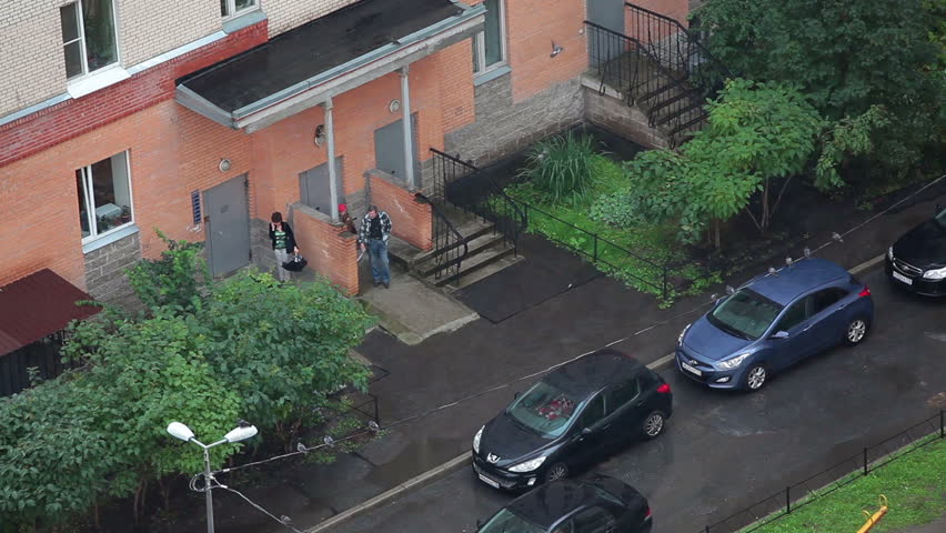 SAINT-PETERSBURG, RUSSIA - CIRCA AUGUST, 2014: People stand under apartment porch roof when rain is falling. Typical inner yards at building with apartments in Russia