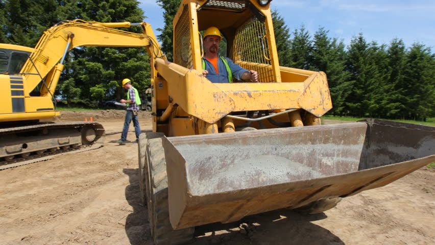 Construction worker driving excavation equipment