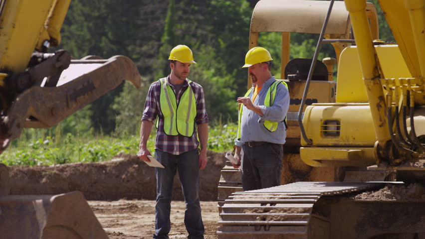 Two workers talking by machinery