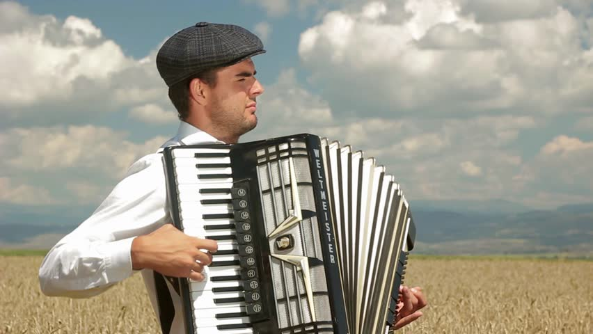 A man is playing the accordion amid a wheat field.