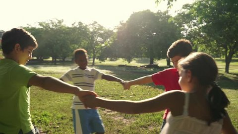 Hispanic and african american little boys and girls playing ring around the rosie in city park and holding hands. Young kids, friends, people, recreation, summer camp fun. Slow motion. 7of18