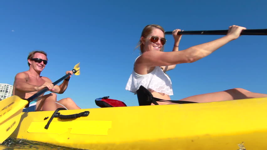 Blonde Couple Kayaking In Ocean