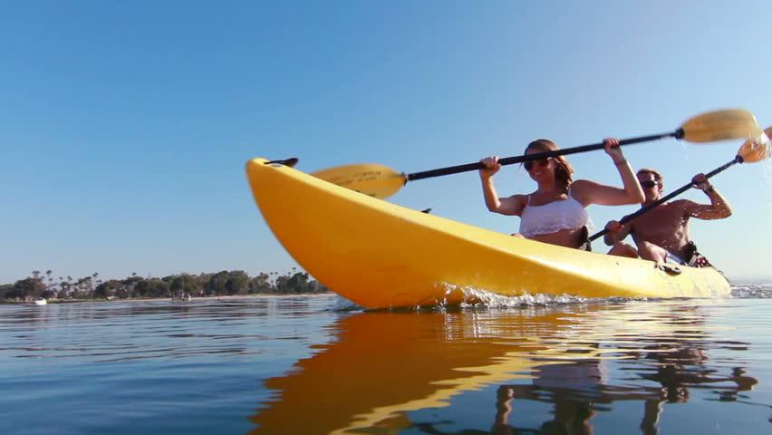 Young Couple Kayaking In Ocean