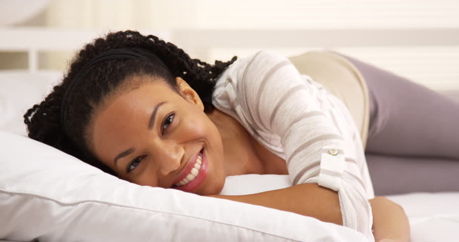 Cute african woman lying on bed looking at camera | Shutterstock HD Video #7320622