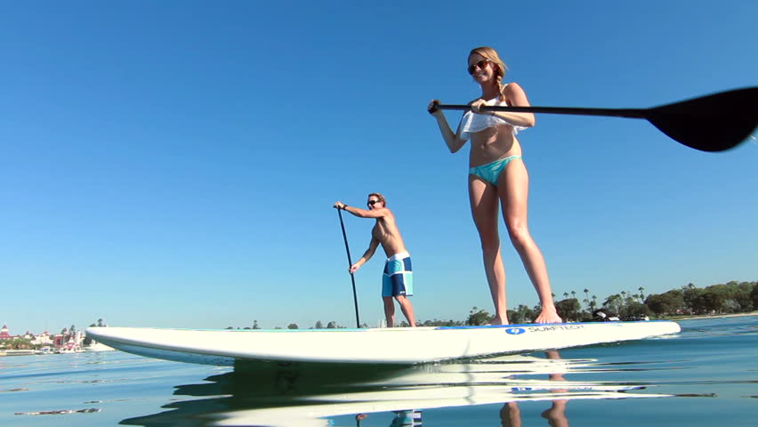 Young Couple Stand Up Paddle Surfing In Ocean