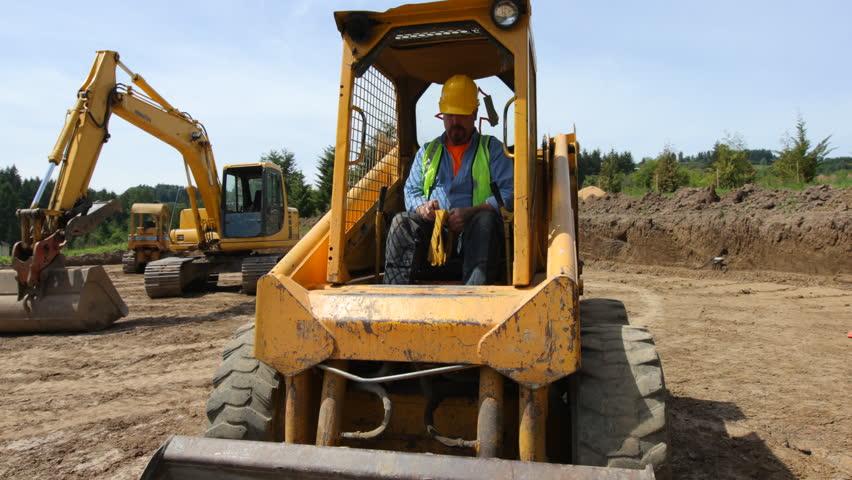 Worker climbs into skid steer excavator