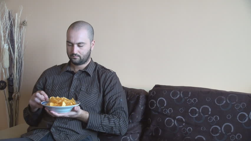 Man at home eating flavored potatoes chips, TV watching, junk food, sits on couch, lazy man