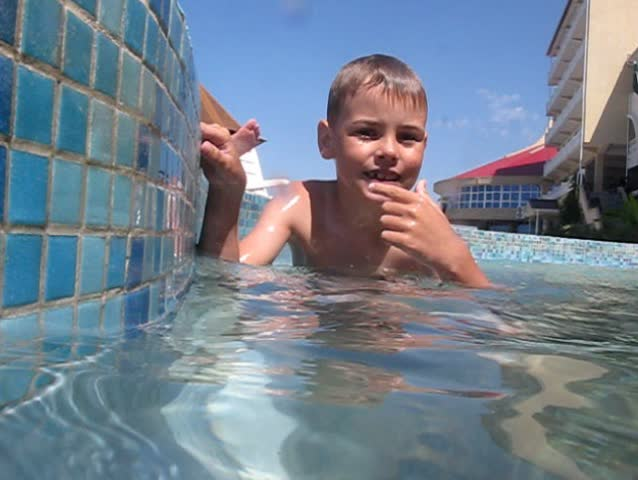 little boy closed his nose diving into swimming pool, underwater survey