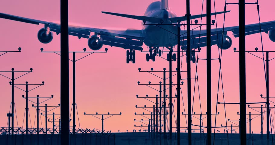 Jumbo jet airplane plane landing in airport in Los Angeles at sunset sunrise. 4K.