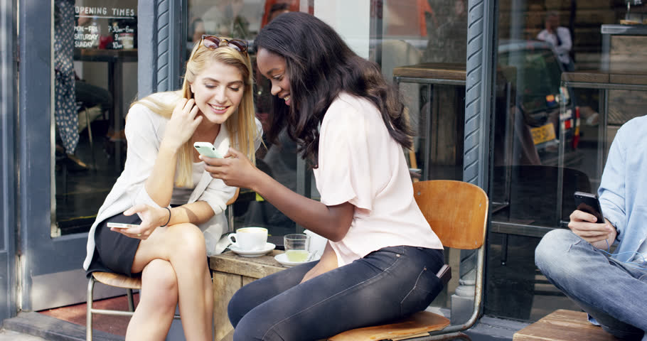 Female friends sharing together using smartphone in urban cafe | Shutterstock HD Video #7374763