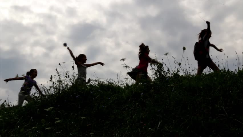 Silhouette of children. Group of children playing on the field. Young girls and boy running on right over the hill. Young boy leads a group of little girls. Childhood. Kids. Teens. Cloudy sky. 25 fps. | Shutterstock HD Video #7377889