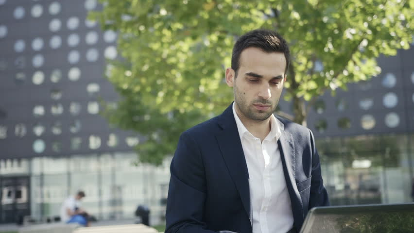 Young handsome and self-confident businessman sitting on a bench in a park near office and using laptop #7382932