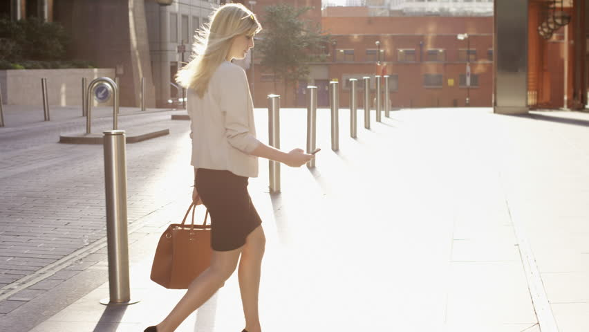 Attractive blonde business woman using smartphone commuting in city london - RED EPIC DRAGON 6K