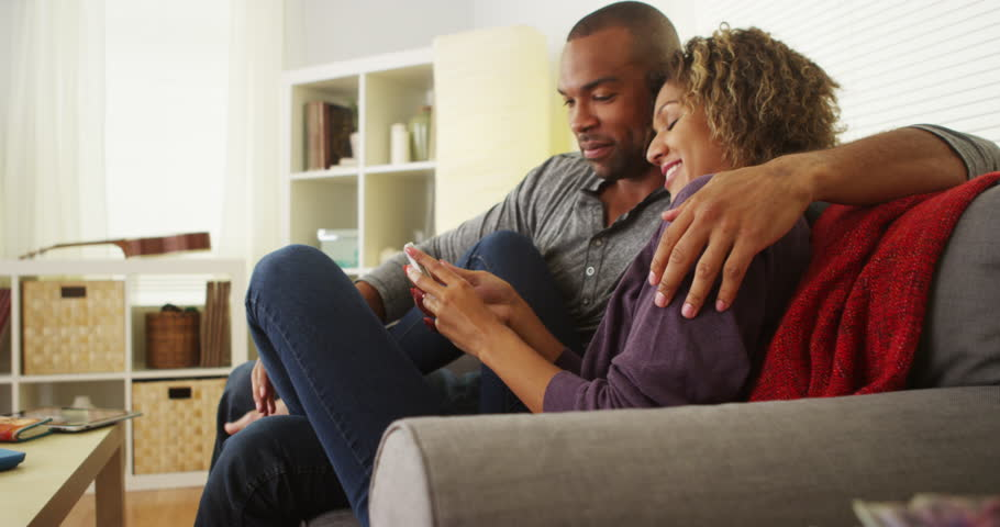 African American couple using devices on couch #7400581