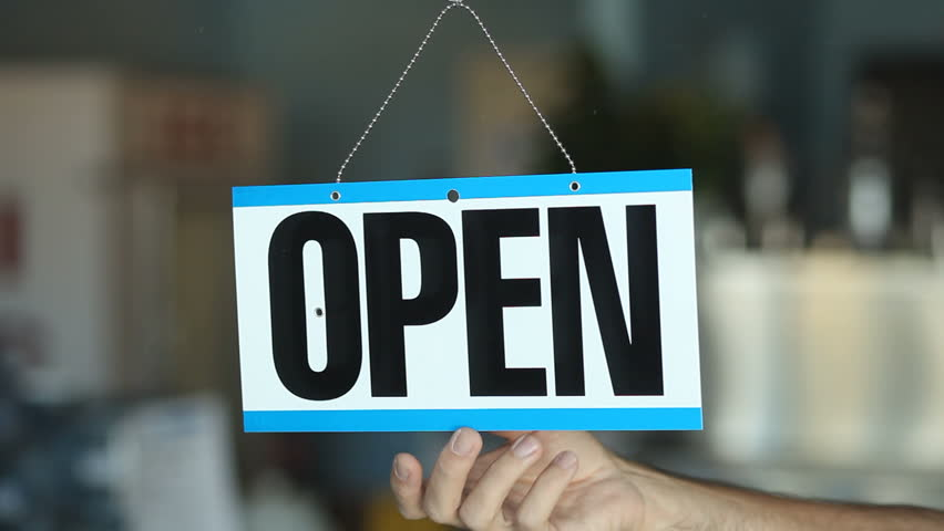 Business Owner Turning An Open For