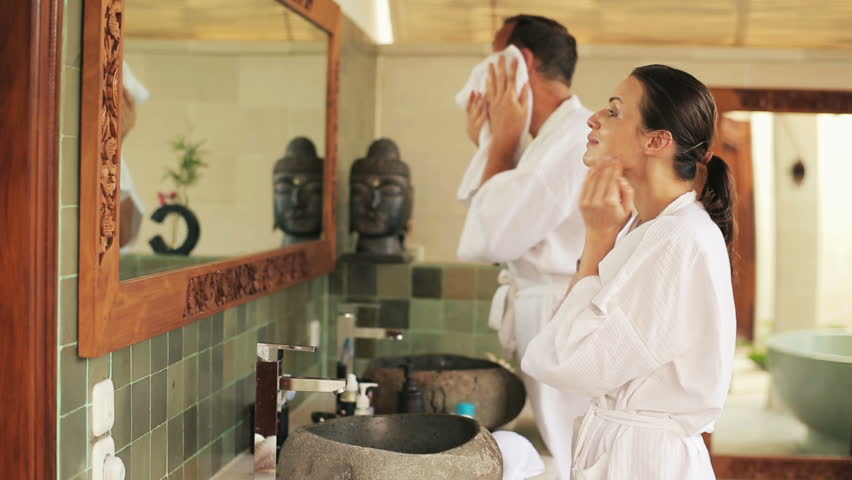 Woman applying cream on her face, husband washing face in bathroom  #7413577