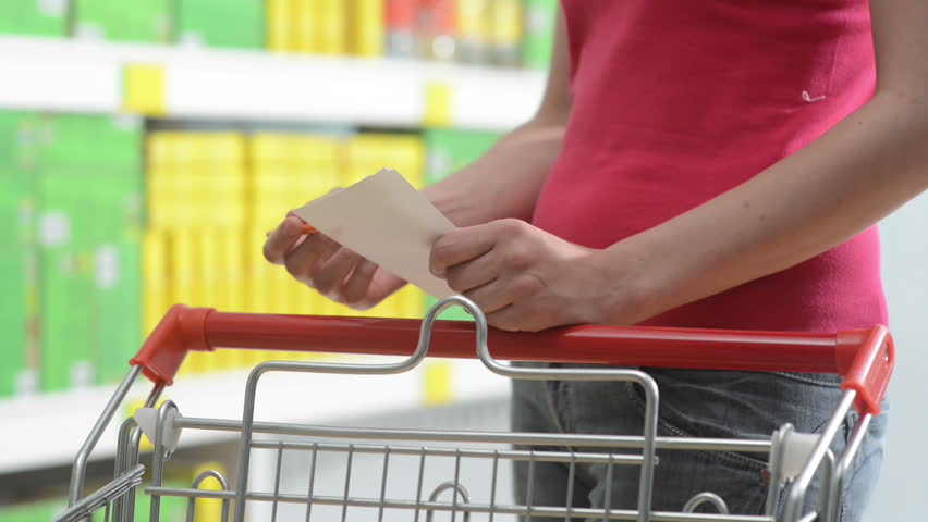 Young woman shopping with trolley at supermarket and checking a paper list. | Shutterstock HD Video #7435318