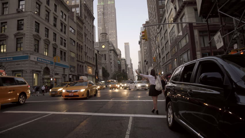 NEW YORK - SEPT 5, 2014: woman hailing taxi cab with Empire State Building and 5th Ave traffic in 4K in Manhattan, New York City. Fifth Avenue is a major thoroughfare in Manhattan NYC USA.