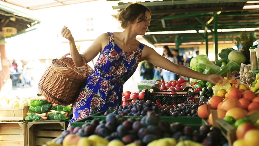 Woman putting tomatoes and peaches to the basket on the market
