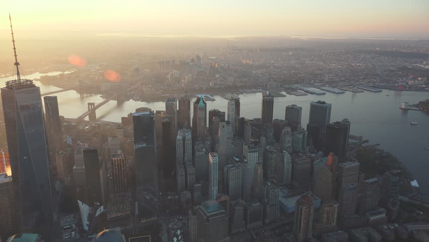 New York City sunrise and early morning light Financial District aerial. Crossing to East River B Bridge. 4K, dedicated plane, hard mounted open window allows a saturated, clear edge on the shot.