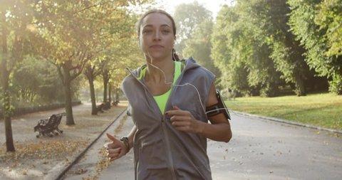 Runner woman running in park exercising outdoors fitness tracker wearable technology