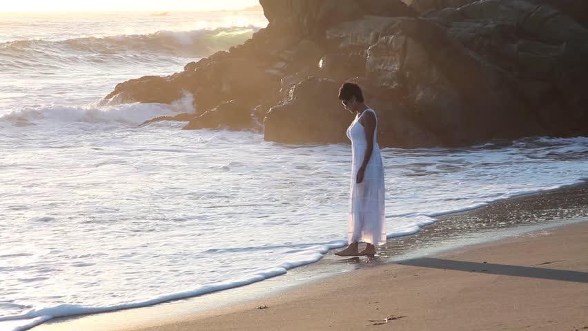 Woman walking near shore at beach with waves crashing   Shutterstock HD Video #7466620