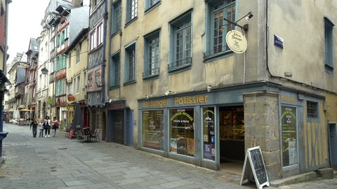 RENNES FRANCE - AUGUST 2014: A traditional boulangerie and patisserie shop on one of the oldest streets in the city. People with children snacking on fresh bread as they walk the pedestrian street.