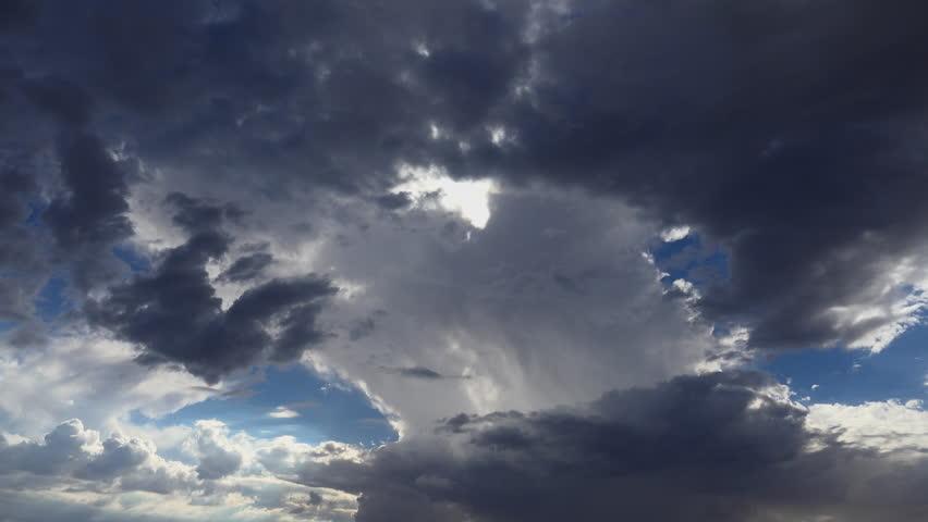 Time Lapse, Dark storm cloud emits rain shaft in blue sky, beautifully backlit by emerging sun. 4K UHD 3840x2160