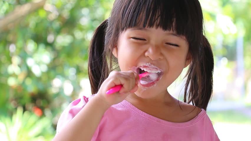 Cute Asian Little Girl Brushing Teeth