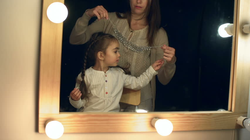 Mother fitting necklace to her daughter in front of the lighted make up mirror in the dark room | Shutterstock HD Video #7501570