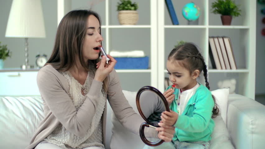 Mother showing daughter lipstick applying technique, girl failing to rouge correctly but having lots of fun | Shutterstock HD Video #7501573
