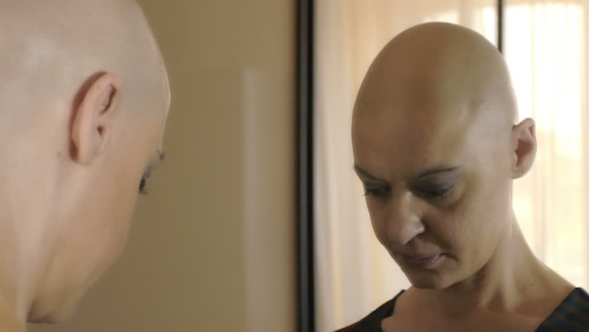 sad woman suffering from cancer at the mirror thinking: loneliness, fear,