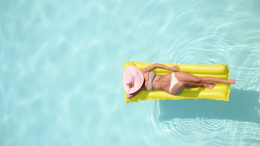 Beautiful young woman relaxing on a yellow inflatable mattress in a swimming pool - Pretty model with perfect shapes chilling out in a exotic resort | Shutterstock HD Video #7525861