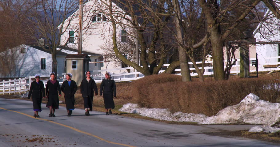 PENNSYLVANIA - CIRCA 2014 - Amish girls walk along a road in rural Pennsylvania.