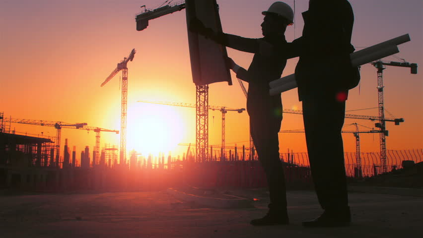Steadicam shot of skyline and cranes with Asian construction/ executive/ architect/ engineer consultant discussing blue print of new urban development with caucasian construction executive at sunset. | Shutterstock HD Video #7579555