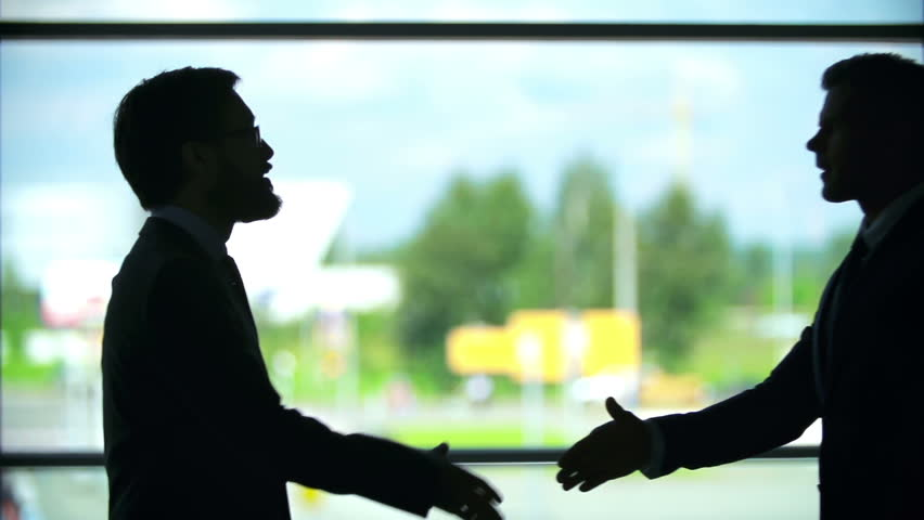 Outlines of two businessmen shaking hands near the window | Shutterstock HD Video #7589857