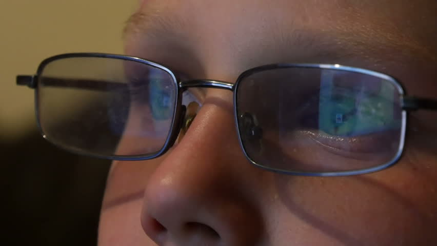 boy in glasses looking at the monitor and the monitor is reflected in the glasses