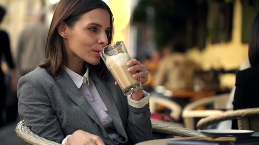Happy successful businesswoman, drinking coffee and sitting in cafe