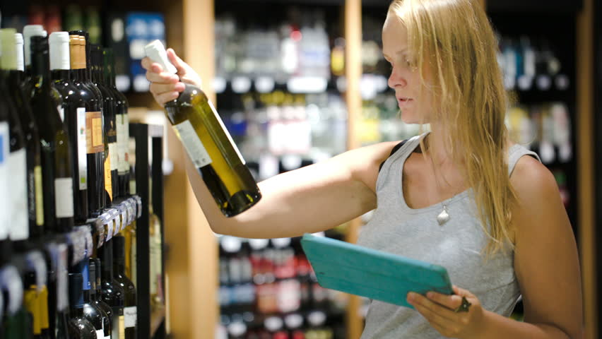 Woman In The Store Choosing Wine According Check List Or Information In Tablet Computer