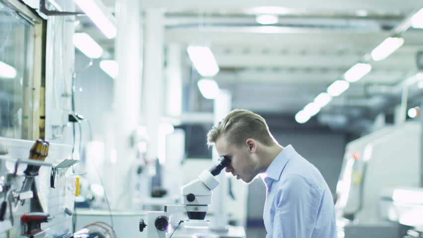 Engineer Inspects Detail Quality under Microscope on Factory. Shot on RED Digital Camera in 4K, so you can easily crop, rotate and zoom. ProResHQ codec - Great for editing, color correction.  | Shutterstock HD Video #7607710