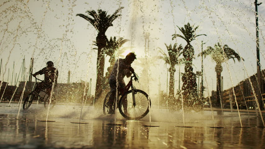 Young boys on bikes cooling off in fountain in the city in summertime