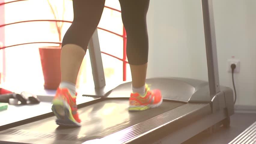 Sport woman legs on treadmill in gym #7626235