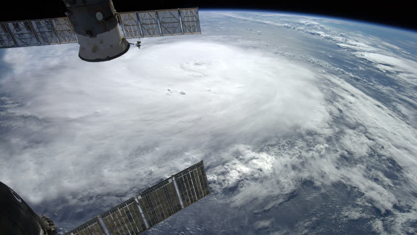 Large typhoon / hurricane framed by two orbiting satellites. #7635508