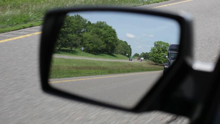 A black 18 wheeler seen in rearview mirror on interstate 81 in  Virginia