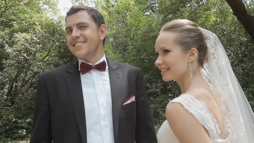 Newlyweds have fun, enjoy each other and kiss in the park | Shutterstock HD Video #7649836