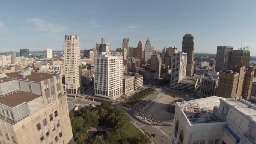 Low flying aerial between Detroit city buildings.