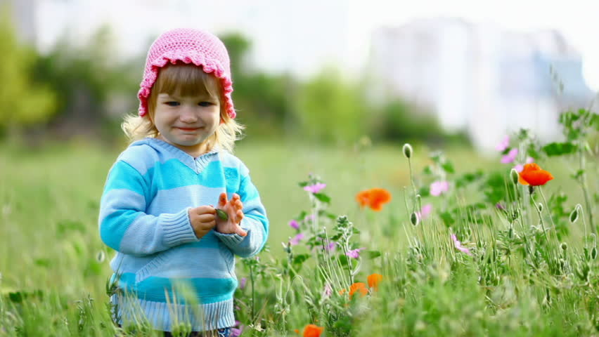 Child smiles, walks on the field