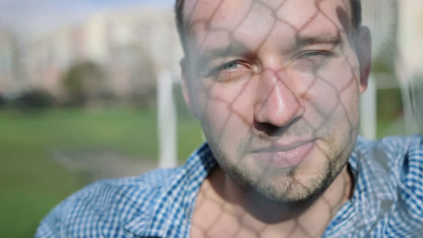 Attractive young man in an urban lifestyle smiling leaning against a modern fence wall, outdoor. #7665577
